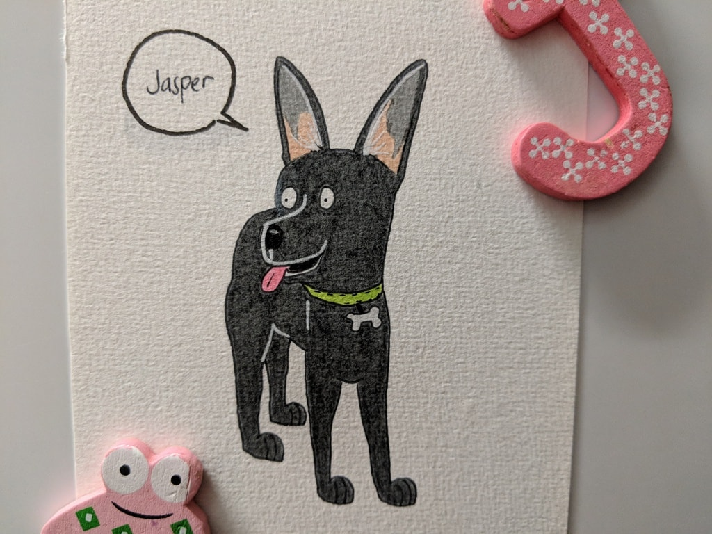 Finished drawing of Jasper the black kelpie. His pink tongue is poking out and he's wearing a green collar with a little bone shaped name tag.