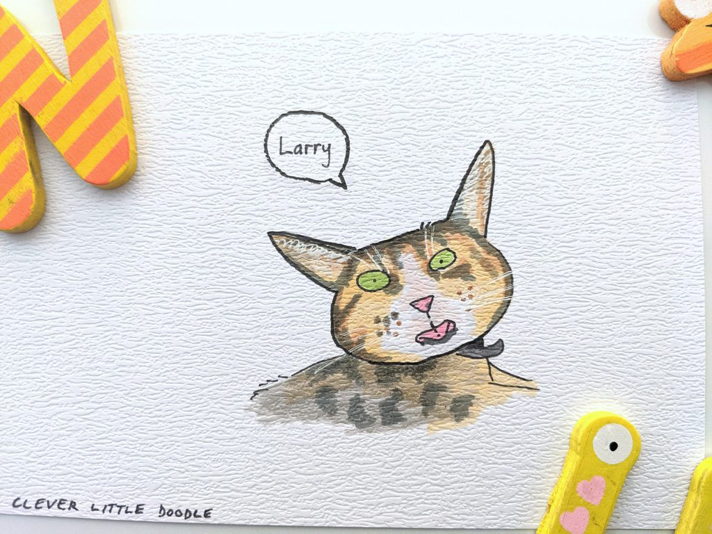 Larry the Domestic Shorthair cat has green eyes, a light brown/tan coloured coat with grey stripes, and a white nose and chin. The cheeky boy is poking his tongue out!